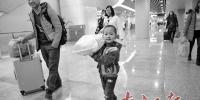 在佛山西站,小朋友帮家人扛着行李进站乘车。南方日报记者 戴嘉信 摄 - 新浪广东