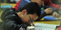 高度近视的孩子趴在桌上写字。(钟小丰  摄) - Meizhou.Cn